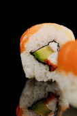 selektivní zaměření čerstvé lahodné Philadelphia sushi kus s avokádem, krémový sýr, losos a masago kaviár izolované na černé