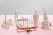 Photo toy airplane near small statuettes of different countries on grey and pink