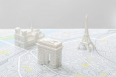 Photo selective focus of small figurines on map of paris isolated on grey