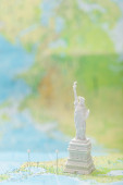 small statue of liberty on map of usa with pins