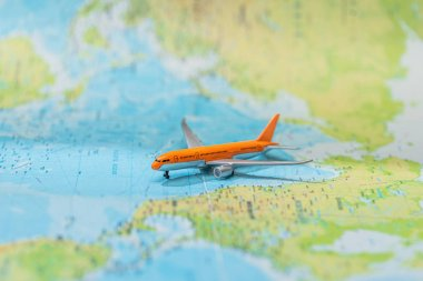 Selective focus of toy plane on world map stock vector