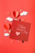 horní pohled na papírové srdce ve tvaru vzduchové balónky v mracích v blízkosti karty s šťastný valentines den nápisy na červeném pozadí