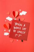 horní pohled na papírové srdce ve tvaru vzduchové balónky v mracích v blízkosti karty s vámi re a lot of lovely yes, vy nápisy na červeném pozadí