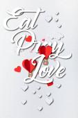 horní pohled na papírové srdce ve tvaru vzduchové balónky v blízkosti jíst modlit láska nápisy na bílém pozadí