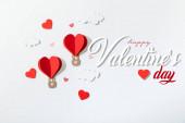 horní pohled na papírové srdce ve tvaru vzduchové balónky v mracích v blízkosti šťastný valentines den nápisy na bílém pozadí