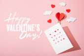 top view of greeting card with hearts near paper heart shaped air balloon in clouds and  happy valentines day lettering on pink