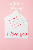 top view of greeting card with hearts in white envelope with i love you lettering on pink