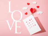 horní pohled na blahopřání se srdcem v blízkosti papírové srdce ve tvaru vzduchový balón v mracích a láska je vše, co potřebujete nápis na růžové