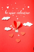 horní pohled na papírové srdce ve tvaru vzduchový balón v mracích v blízkosti důl valentine písmo na červeném pozadí