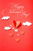 top view of paper heart shaped air balloon in clouds near happy valentines day lettering on red background