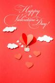 felső nézet papír szív alakú léggömb felhők közelében boldog Valentin-nap felirat piros háttér