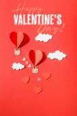 horní pohled na papírové srdce ve tvaru vzduchové balónky v mracích v blízkosti šťastný valentines den nápisy na červeném pozadí