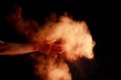 ženské ruce v blízkosti oranžové barevné holi barva exploze na černém pozadí