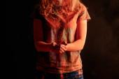 oříznutý pohled na ženu s oranžové barevné holi barva prášek izolovaný na černé