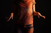 cropped view of woman with orange colorful holi paint powder on body and clothes isolated on black