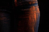 Fotografie cropped view of woman with orange colorful holi paint powder on jeans isolated on black
