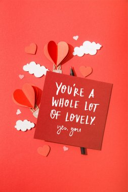 top view of paper heart shaped air balloons in clouds near card with you're a whole lot of lovely yes, you lettering on red background