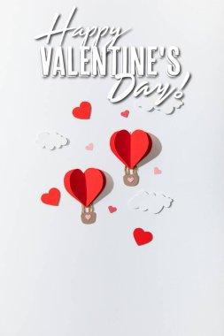 Kağıt kalbin üst görüntüsü bulutlardaki hava balonları mutlu sevgililer günü arkaplanda beyaz harflerle yazılmış.