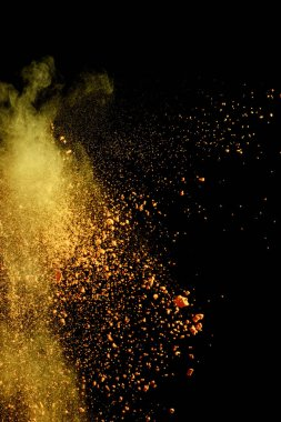 Yellow colorful holi paint explosion on black background stock vector