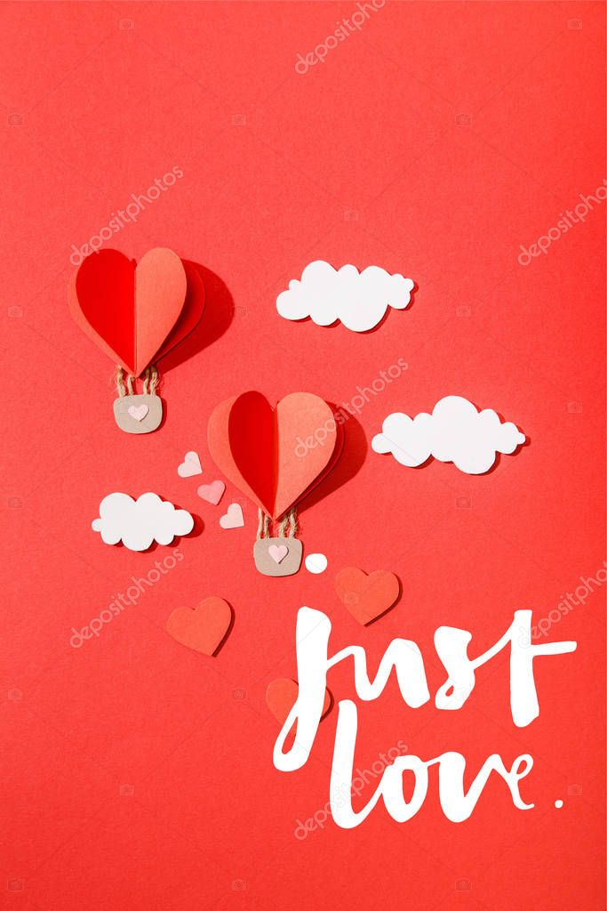 Top view of paper heart shaped air balloons in clouds near just love lettering on red background stock vector