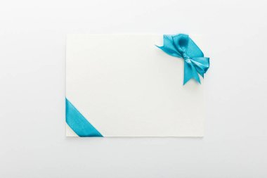 Top view of blank card with blue decorative satin ribbon and bow on white background stock vector