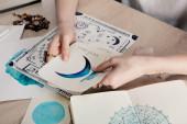 Oříznutý pohled na astrolog držící karty s akvarelovými kresbami podle rodné mapy se zvěrokruhovým znakem na stole