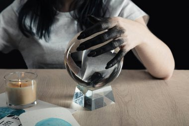 Cropped view of magician with black painted hand holding crystal ball by watercolor paintings and candle on table isolated on black stock vector