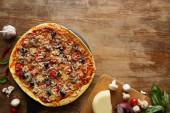 Horní pohled na pizzu a zeleninu na dřevěném pozadí