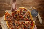 Fotografie Oříznutý pohled na pár jíst pizzu na dřevěném pozadí