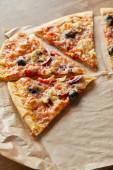 Fotografie krájet lahodnou italskou pizzu s olivami na pečení papíru na dřevěném pozadí