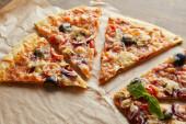 krájet lahodnou italskou pizzu s olivami na pečicím papíru na dřevěném stole