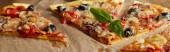 Fotografie krájet lahodnou italskou pizzu s olivami a bazalkou na pečicím papíru na dřevěném stole, panoramatický záběr
