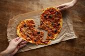oříznutý pohled na pár drží lahodnou italskou pizzu v zlomeném tvaru srdce na pečení papíru u dřevěného stolu