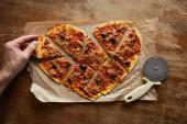 Fotografie oříznutý pohled na člověka jíst lahodnou italskou pizzu ve tvaru srdce krájené na kousky na pečení papíru v blízkosti pizza nůž na dřevěném stole