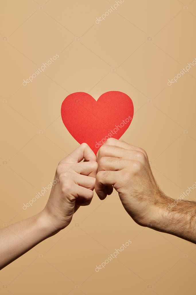 Cropped view of man and woman holding red heart isolated on beige stock vector