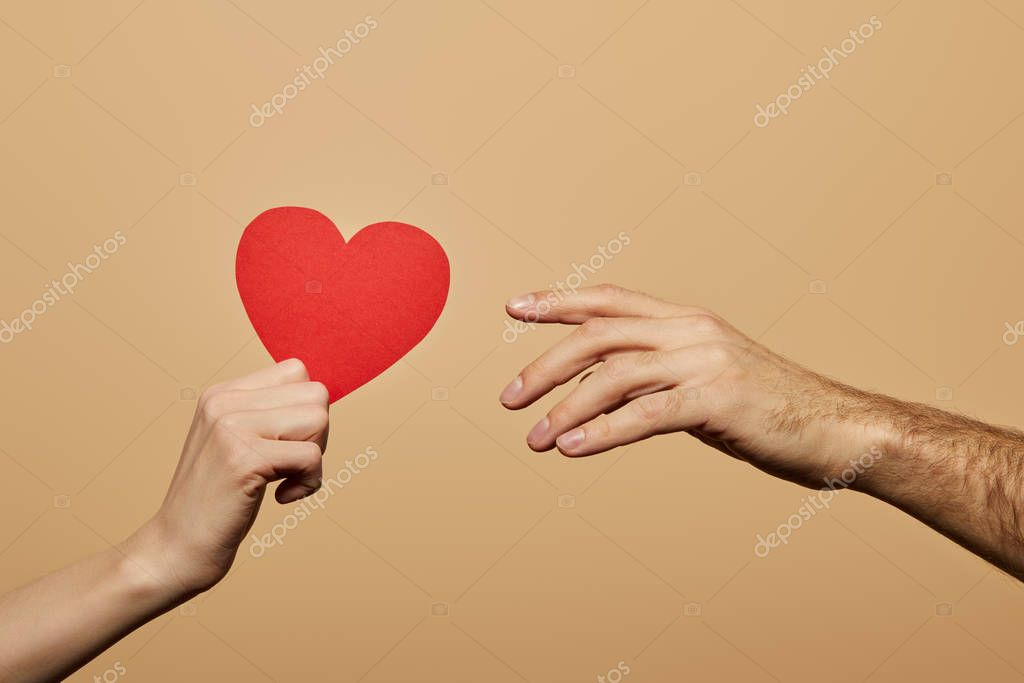 Cropped view of woman holding red heart and man reaching it isolated on beige stock vector