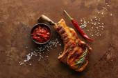 Horní pohled na ribeye steak s rajčatovou omáčkou, rozmarýnem a chilli paprikou na kamenném povrchu