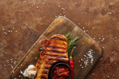Top view of tasty steak with chili sauce, garlic and rosemary on cutting board on stone background