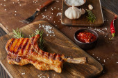 Selective focus of ribeye steak on cutting board with chili sauce, garlic and salt on stone board on wooden surface