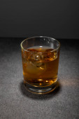 fagyasztott jégkockák egy üveg whiskey-ben szürke felületen