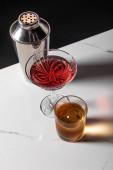 Draufsicht auf Gläser mit alkoholischen Getränken in der Nähe von Shaker auf Marmoroberfläche isoliert auf schwarz