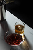 Photo selective focus of glass with whiskey near red wine and shaker isolated on black