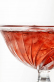 close up of red cocktail with ice cubes isolated on white