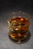 jégkockák egy pohár alkoholtartalmú italban szürke felületen