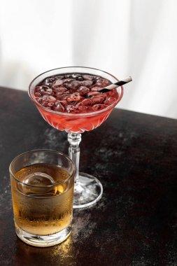 Glass of whiskey near cosmopolitan cocktail on white stock vector