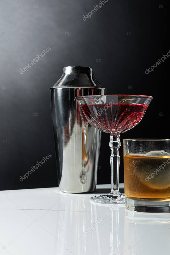 Glass of strong whiskey near red wine and shaker on black with smoke stock vector