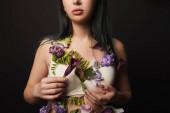 oříznutý pohled na krásnou dívku v podprsence s fialovými a fialovými květy na těle izolované na černé