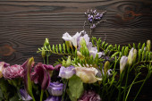 top view of violet and purple floral bouquet on wooden table
