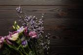 pohled na fialovou a fialovou květinovou kytici na dřevěném stole