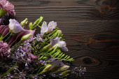 Photo top view of violet and purple floral bouquet on wooden table